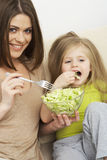Mother feeds little girl Royalty Free Stock Photos