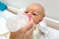 Mother feeds their newborn baby with bottle Royalty Free Stock Photos
