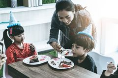 Mother feeing her children birthday cake in a brithday party stock photo