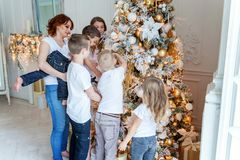 Mother and five children decorating a Christmas tree Royalty Free Stock Images