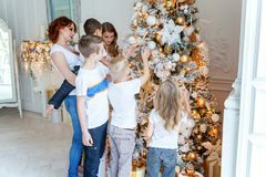 Mother and five children decorating Christmas tree at home royalty free stock image