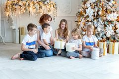 Mother and five children near Christmas tree at home royalty free stock images