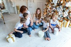 Mother and five children near Christmas tree at home stock photography