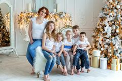 Mother and five children near Christmas tree at home royalty free stock photos