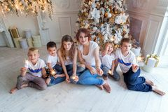 Mother and five children playing sparkler near Christmas tree at home stock photos