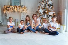 Mother and five children playing sparkler near Christmas tree at home stock photography