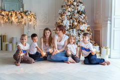 Mother and five children playing sparkler near Christmas tree at home royalty free stock images
