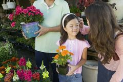 Mother fixing hair of daughter in plant nursery Royalty Free Stock Image