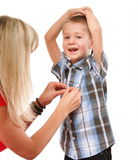 Mother fixing young boy's shirt Royalty Free Stock Photography