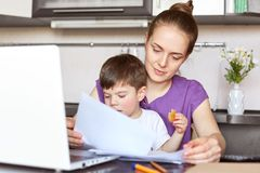 Mother freelancer on maternity leave works with documentation, makes business report on portable laptop computer, holds son who in. Terrupts her, sit together stock photo