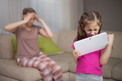 Mother frustrating that her daughter  playing video games. Mother frustrating that her daughter playing video games. Happy child girl and sad mother Stock Image