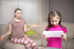 Mother frustrating that her daughter playing video games. Royalty Free Stock Image