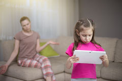 Mother frustrating that her daughter playing video games. Stock Photography