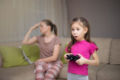 Mother frustrating that her doughter playing video games. stock photo