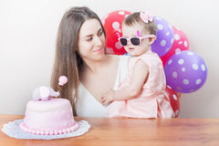 Mother with funny baby celebrating first birthday. Cake. Mother with funny baby celebrating first birthday. Cake is surprise for child. Make a first wish Royalty Free Stock Photo