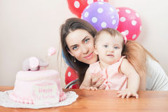 Mother with funny baby celebrating first birthday. Cake. Mother with funny baby celebrating first birthday. Cake is surprise for child. Make a first wish Stock Image