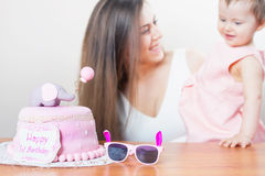 Mother with funny baby celebrating first birthday. Cake. Mother with funny baby celebrating first birthday. Cake is surprise for child. Make a first wish Royalty Free Stock Photography