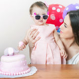 Mother with funny baby celebrating first birthday. Cake. Mother with funny baby celebrating first birthday. Cake is surprise for child. Make a first wish Stock Photo