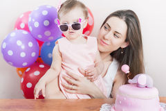 Mother with funny baby celebrating first birthday. Cake. Mother with funny baby celebrating first birthday. Cake is surprise for child. Make a first wish Stock Photography