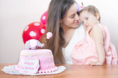 Mother with funny baby celebrating first birthday. Cake. Mother with funny baby celebrating first birthday. Cake is surprise for child. Make a first wish Stock Photos