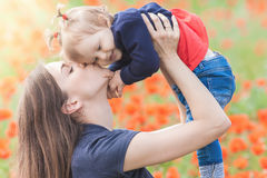 Mother with funny child outdoor at poppy flowers field Stock Image