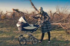 Mother in Gas Mask with Baby Buggy. Mother wearing gas mask giving toy to a child in pushcart, looking at the camera and standing in sorroundings of leafless Stock Photos