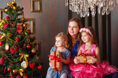 Mother gave Christmas gifts to two daughters. Stock Photos