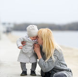 Mother gently embraces and kisses the little daughter. Royalty Free Stock Photography