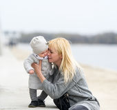 Mother gently embraces and kisses the little daughter. Stock Images