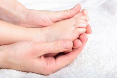 Mother gently hold baby's leg Stock Image