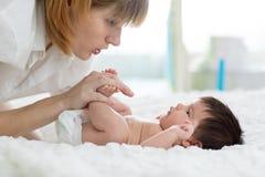 Mother gently massaging her baby`s feet. Motherhood and children health concept Stock Image