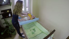 Mother getting dressed her baby with yellow body cloth. 4K stock video