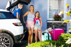 Family vacation suitcases Labrador dog girl kid baggage blue pink orange house sun summer luggage car ready holidays green trank b. Mother, girl and boy are Royalty Free Stock Images