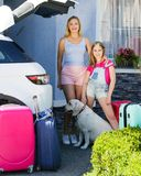 Family vacation suitcases Labrador dog girl kid baggage blue pink orange house sun summer luggage car ready holidays green trank b. Mother, girl and boy are Stock Image