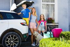 Family vacation suitcases Labrador dog girl kid baggage blue pink orange house sun summer luggage car ready holidays green trank b. Mother, girl and boy are Stock Photo