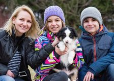 Mother, girl, boy and puppy Stock Photo