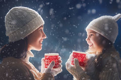 Mother and girl drinking tea. Happy loving family! Mother and child girl drinking tea on snowy winter walk in nature. Frost winter season Stock Image