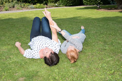 Mother and girl on the grass, mother points to the sky Royalty Free Stock Photo