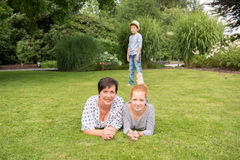 Mother and girl on the grass, small boy in the background Stock Photography