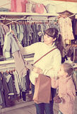 Mother with girl looking for clothing for babies Stock Photo