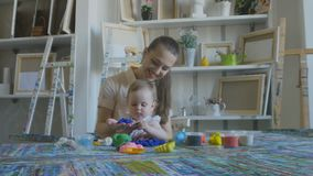 Mother and girl make figures of plasticine and kinetic sand. Young attractive nanny is playing with baby in plasticine. Preschool Development stock footage