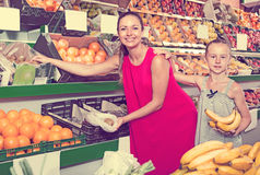 Mother with girl picking different fruits Stock Photos