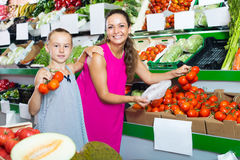Mother with girl picking ripe tomatoes in shop Stock Photo