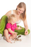 Mother and girl play with coins Stock Photography