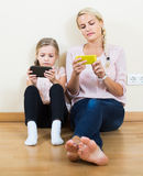 Mother and girl playing with mobile phones indoor Stock Photos