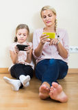 Mother and girl playing with mobile phones indoor Stock Photo