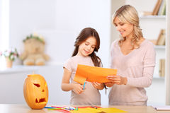 Mother and girl PRAPERING FOR PARTY. Involved in process. Pleasant vivacious mother with daughter craving the paper while going to have celebration Royalty Free Stock Image