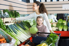 Mother with girl purchasing shallot Stock Images