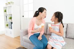 Mother and girl showing tongues to each other. Funny beautiful mother and little girl showing grimace to each other when they eating ice cream together at home Stock Photos