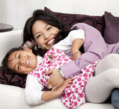 Mother and girl smiling. In the living room white Royalty Free Stock Image